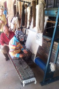 A rug weaver at a cooperative craft business.